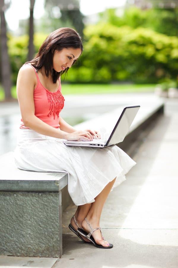 Donna sul telefono e lavorare al suo computer portatile fotografia stock