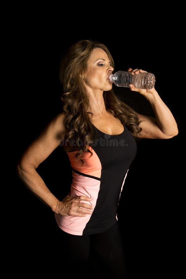 Donna sull'abbigliamento nero di forma fisica dell'acqua potabile fotografia stock libera da diritti