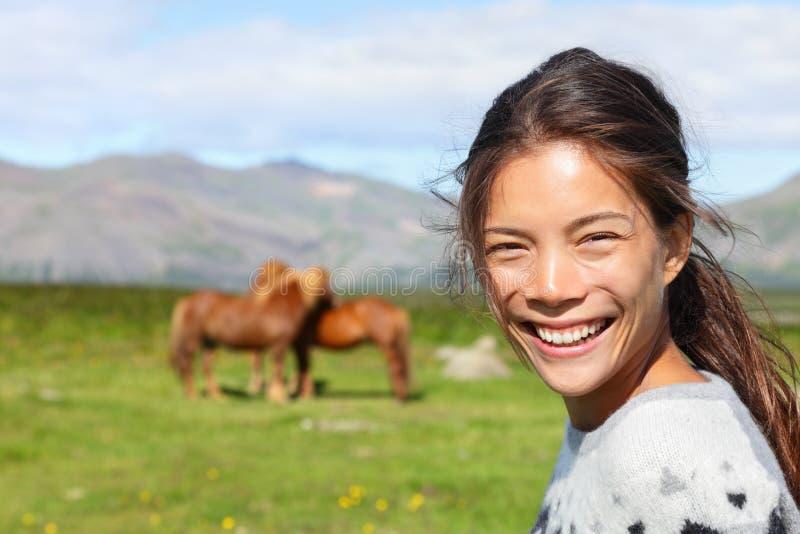 Donna sull'Islanda che sorride con i cavalli islandesi fotografia stock