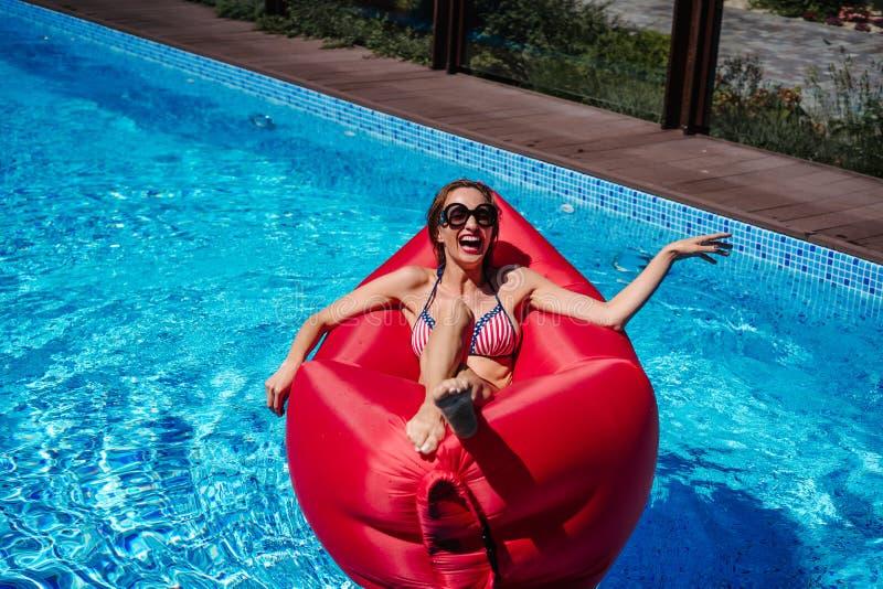Donna sulla chaise-lounge rossa nello stagno immagine stock