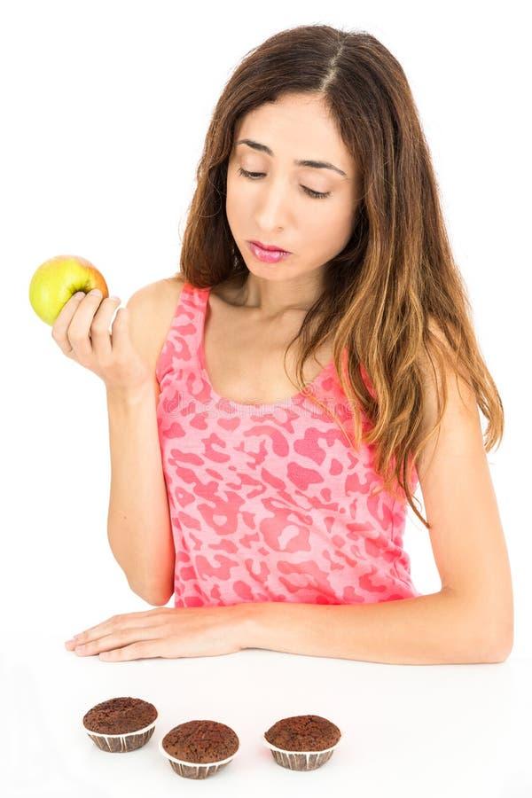 Donna sulla dieta che guarda ai muffin mentre mangiando una mela fotografie stock libere da diritti