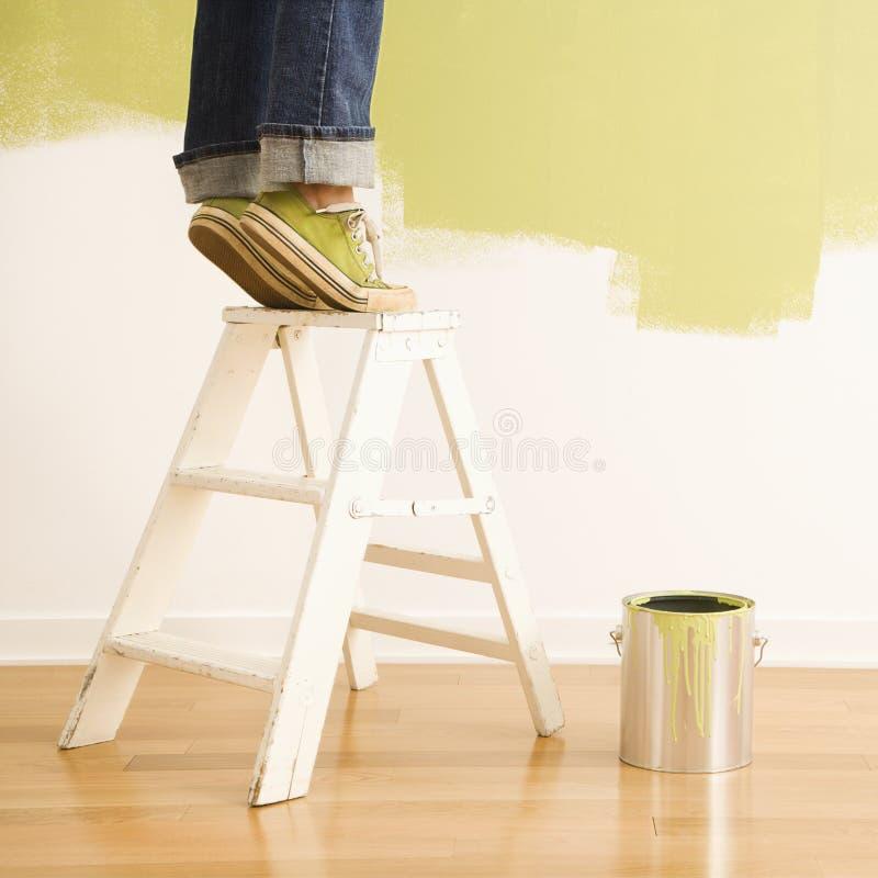 Donna sulla pittura della scaletta. immagini stock