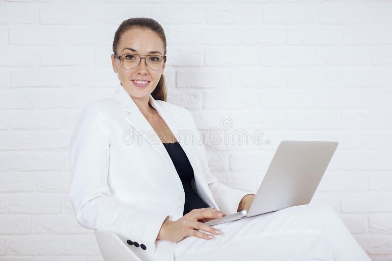 Donna sulla presidenza con il computer portatile immagini stock