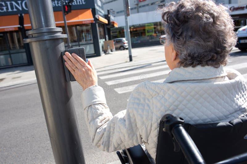 Donna sulla sedia a rotelle che spinge il bottone dell'incrocio fotografie stock
