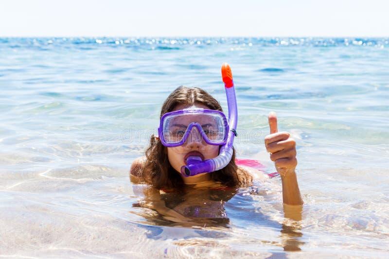 Donna sulle feste di vacanza della spiaggia con la presa d'aria che si trova nel mare con immergersi sorridere della maschera fel immagine stock