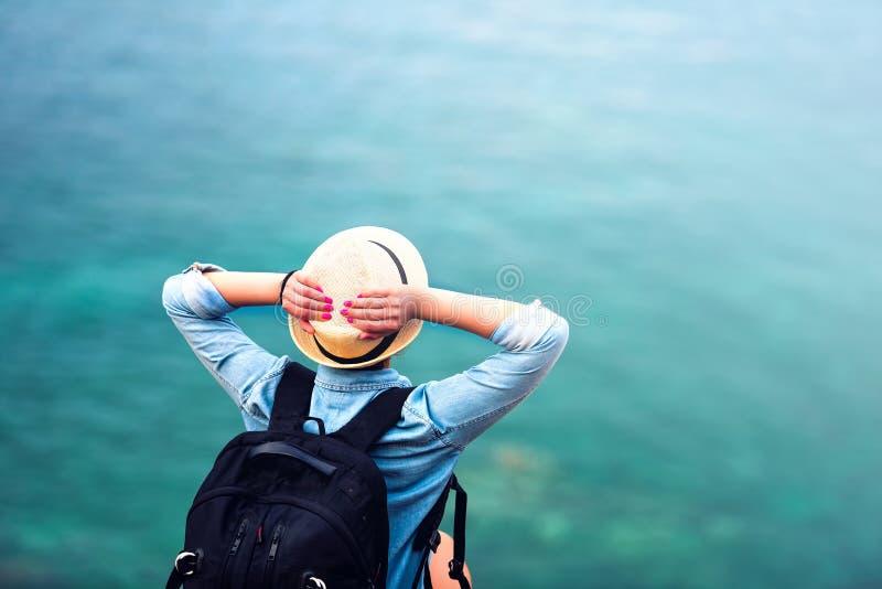 Donna sulle vacanze estive, facenti un'escursione sulla linea costiera e fissanti in mare immagini stock