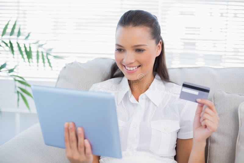 Donna sveglia allegra che compra online facendo uso del suo pc della compressa fotografie stock