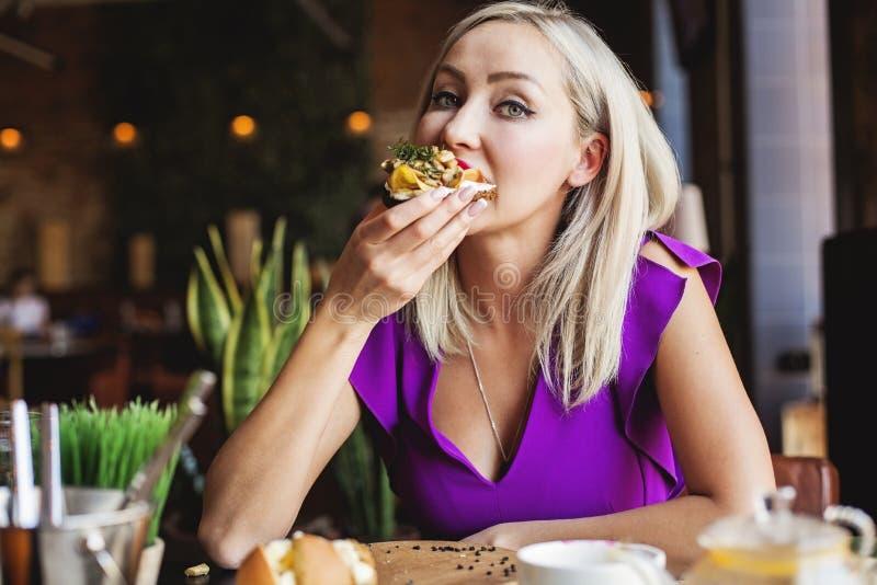 Donna sveglia che mangia smorrebrod danese saporito immagini stock libere da diritti
