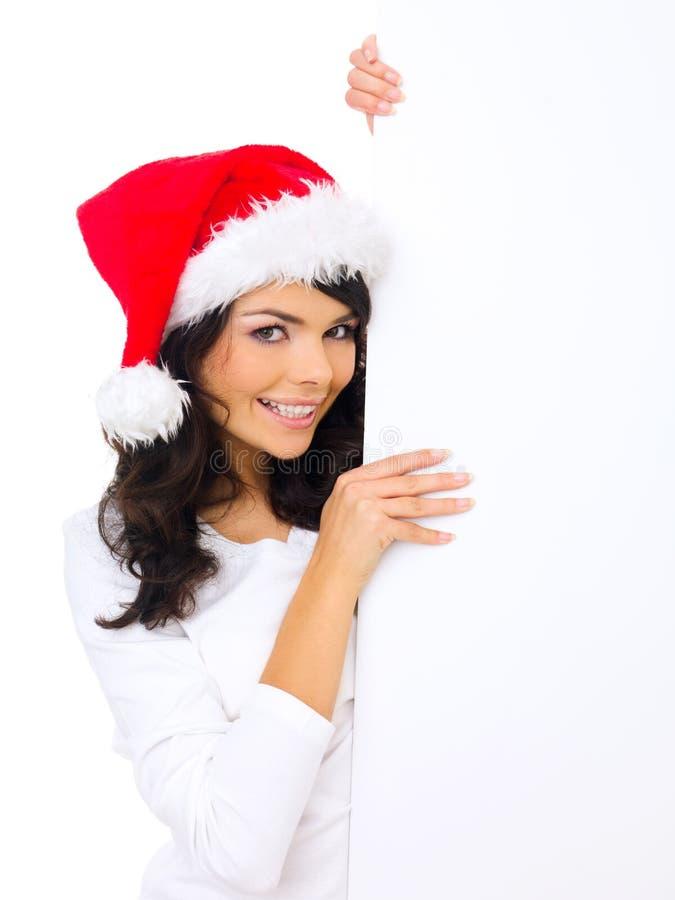 Donna sveglia che porta il cappello di Santa con un segno in bianco fotografia stock
