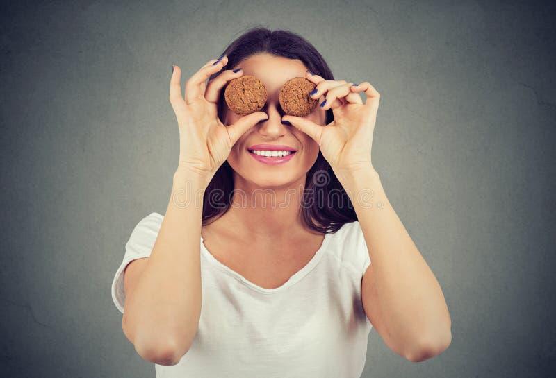 Donna sveglia che tiene i biscotti davanti ai suoi occhi e che sorride felicemente fotografia stock