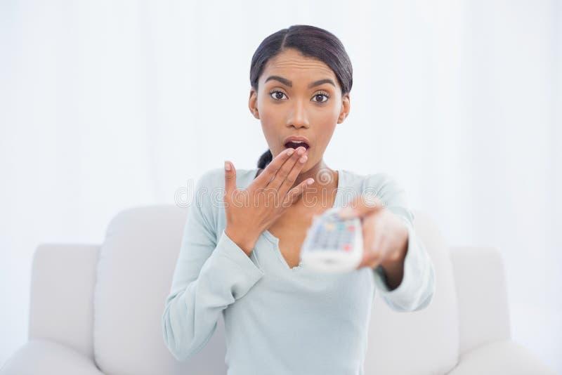Donna sveglia colpita che si siede sul canale televisivo cambiante del sofà fotografie stock