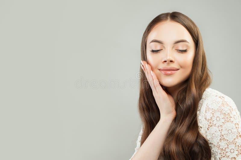Donna sveglia con capelli ricci lunghi e chiara pelle Skincare e concetto facciale di trattamento fotografia stock