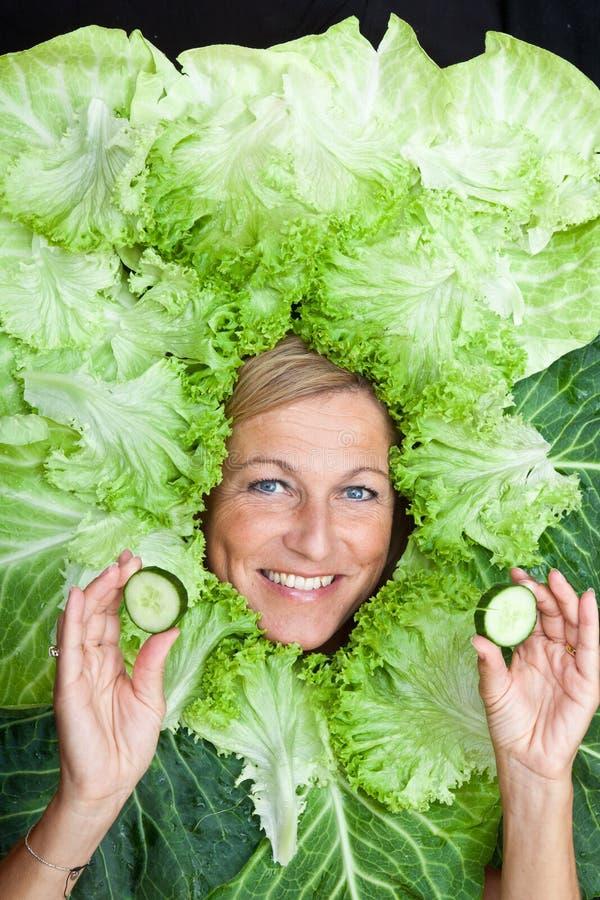Donna sveglia con le foglie dell'insalata sistemate intorno al suo capo, giocando w immagini stock
