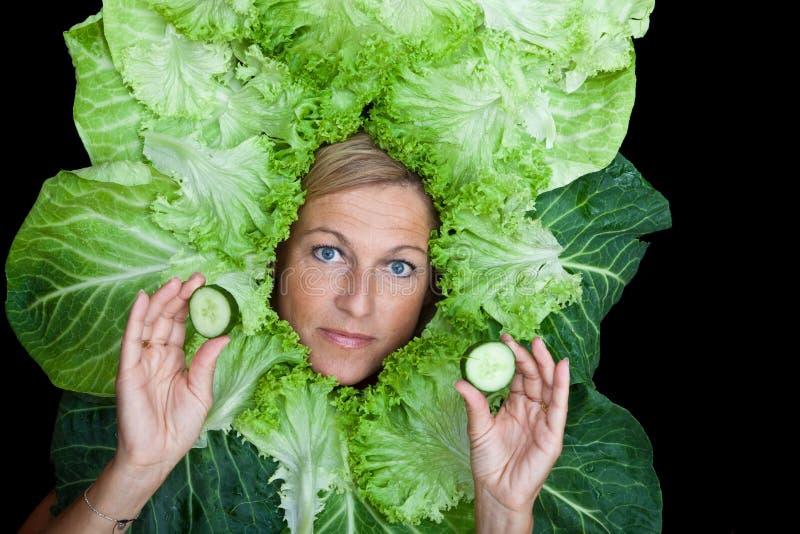 Donna sveglia con le foglie dell'insalata sistemate intorno al suo capo, giocando w immagine stock libera da diritti