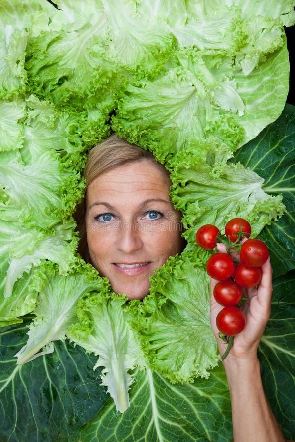 Donna sveglia con le foglie dell'insalata sistemate intorno al suo MP di tenuta capo fotografie stock