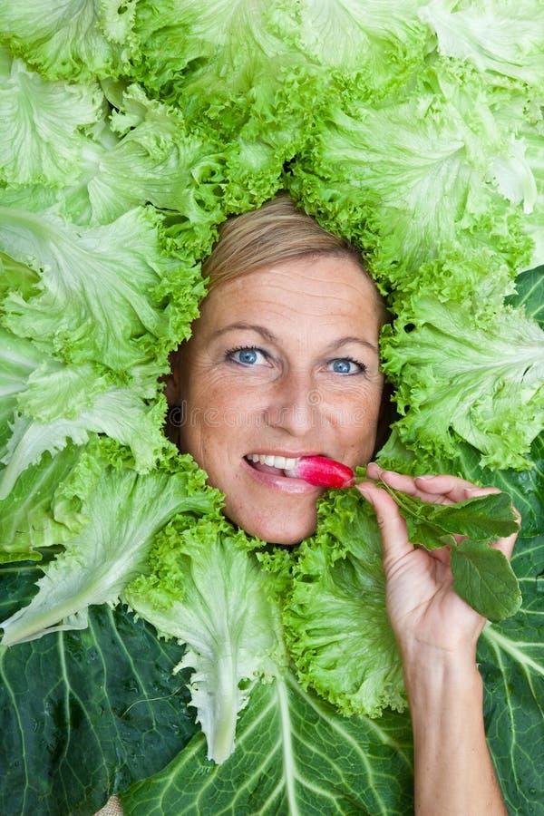 Donna sveglia con le foglie dell'insalata sistemate intorno alla sua testa che mangia una r immagine stock