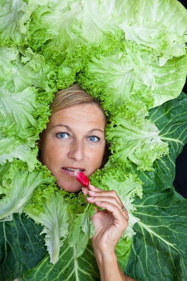 Donna sveglia con le foglie dell'insalata sistemate intorno alla sua testa che mangia una r fotografie stock