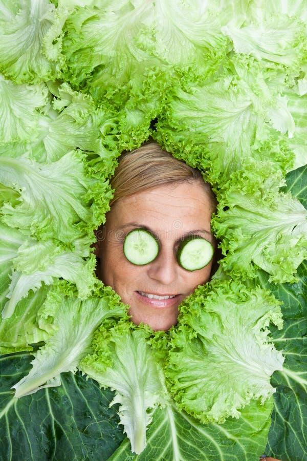 Donna sveglia con le foglie dell'insalata sistemate intorno alla sua testa con il cucum fotografia stock