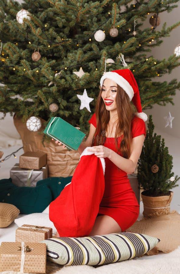 Donna sveglia di Natale che indossa il regalo di Santa Hat Pulls A fotografia stock libera da diritti