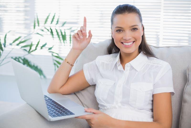 Donna sveglia felice che per mezzo del computer portatile che si siede sul sofà accogliente fotografia stock