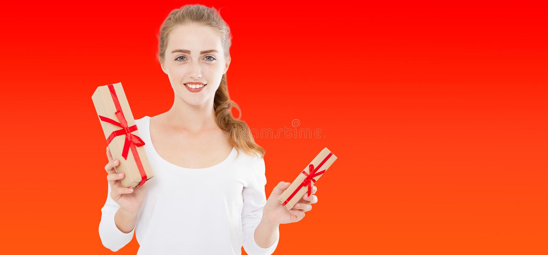 Donna sveglia felice con i regali di natale sopra fondo rosso, falso su fotografia stock