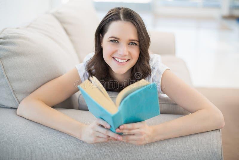 Donna sveglia pacifica che si trova su un libro di lettura accogliente dello strato fotografie stock