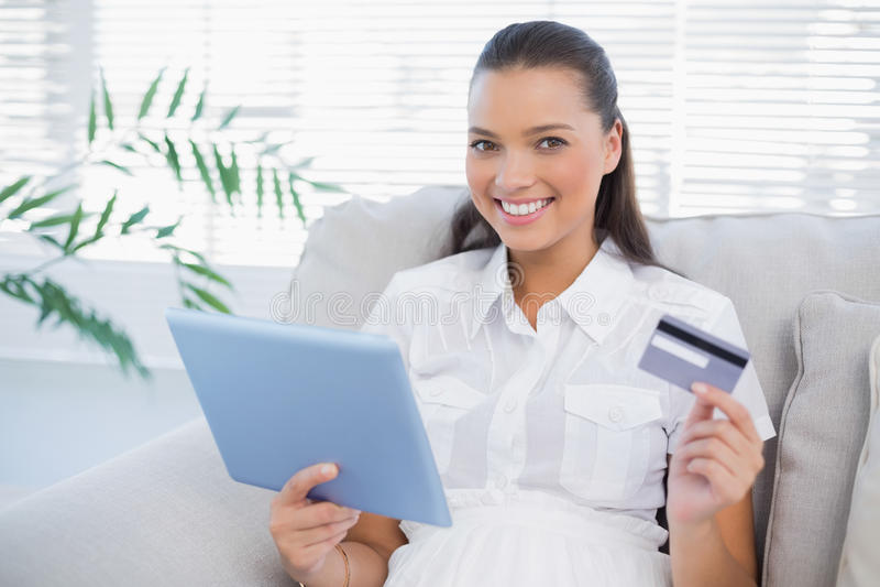 Donna sveglia sorridente che compra online facendo uso del suo pc della compressa fotografie stock