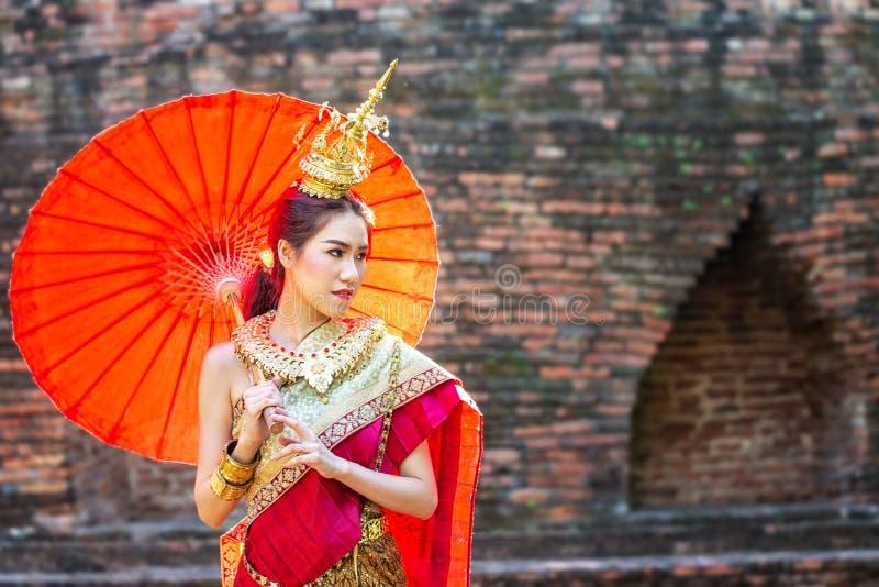 Donna tailandese in costume tradizionale con l'ombrello della Tailandia Costume tradizionale femminile con il fondo tailandese de fotografia stock libera da diritti