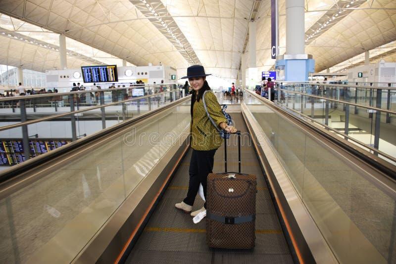 Donna tailandese dei viaggiatori che cammina e trascinare bagagli sulla scala mobile in terminale a Hong Kong International Airpo immagini stock libere da diritti