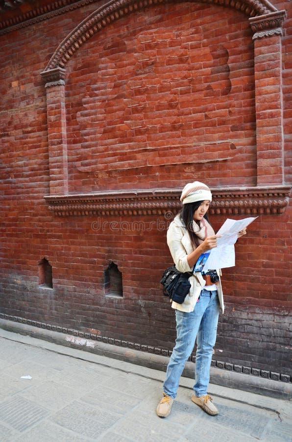 Donna tailandese del viaggiatore con la mappa a Thamel Kathmandu immagini stock libere da diritti