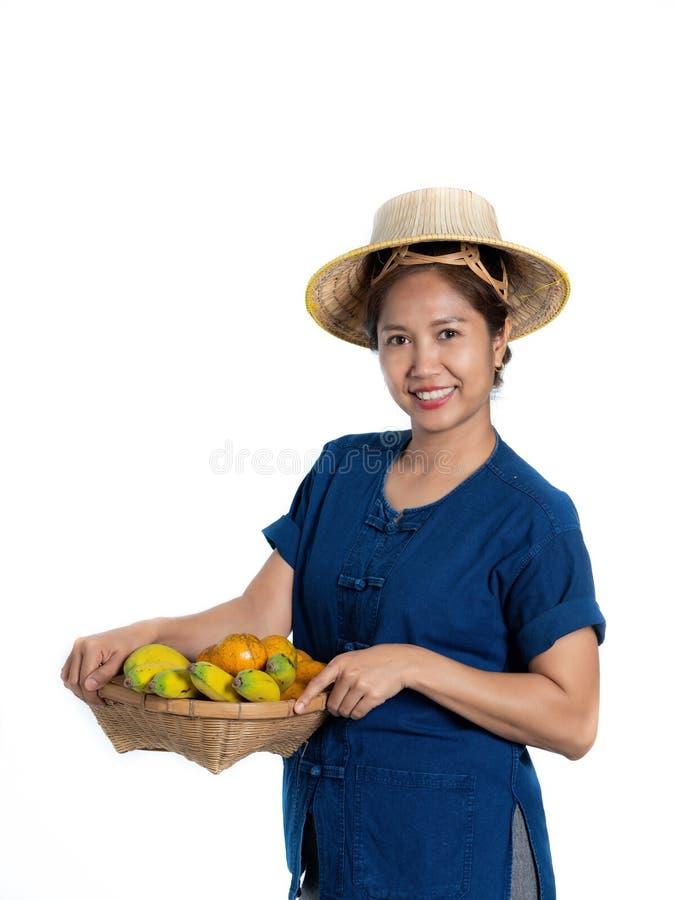 Donna tailandese in vestiti tradizionali e frutti di vendita sulla b bianca immagine stock
