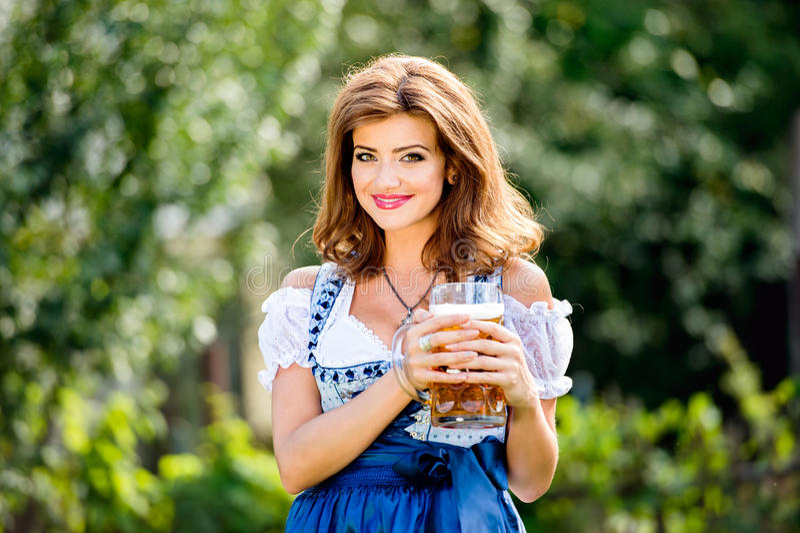 Donna in tazza bavarese tradizionale della tenuta del vestito di birra immagine stock libera da diritti