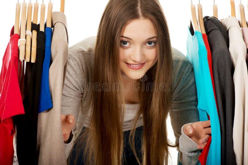 Donna teenager fra i vestiti sul gancio immagini stock libere da diritti