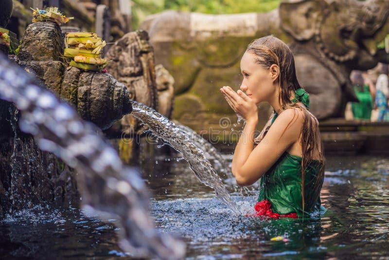 Donna in tempio santo dell'acqua sorgiva in Bali Il composto del tempio consiste di una struttura petirtaan o di bagno, famosa pe fotografie stock libere da diritti