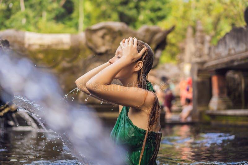 Donna in tempio santo dell'acqua sorgiva in Bali Il composto del tempio consiste di una struttura petirtaan o di bagno, famosa pe fotografia stock libera da diritti