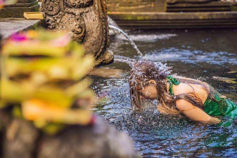 Donna in tempio santo dell'acqua sorgiva in Bali Il composto del tempio consiste di una struttura petirtaan o di bagno, famosa pe immagine stock libera da diritti