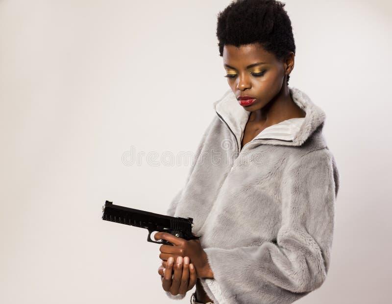 Donna tenendo a disposizione le pistole fotografie stock