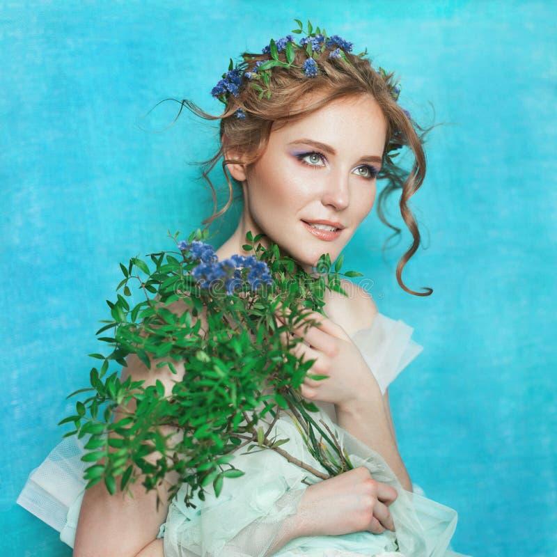 Donna tenera sorridente dei giovani con i fiori blu su fondo blu-chiaro Ritratto di bellezza di primavera fotografia stock