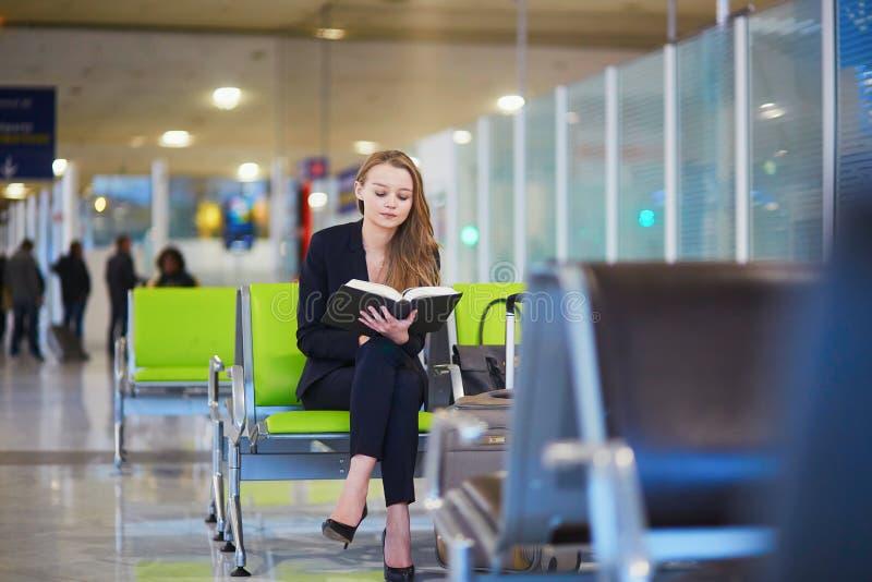 Donna in terminale di aeroporto internazionale, libro di lettura fotografia stock