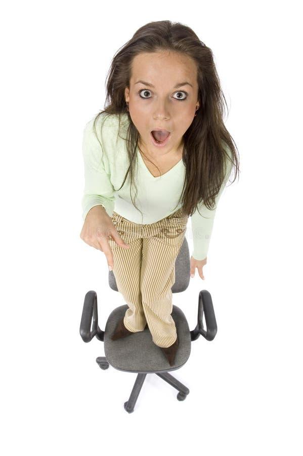 Donna terrorizzata che si leva in piedi sulla presidenza dell'ufficio fotografia stock