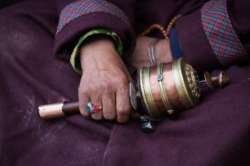 Donna tibetana anziana che tiene la ruota di preghiera buddista, Ladakh, India fotografie stock
