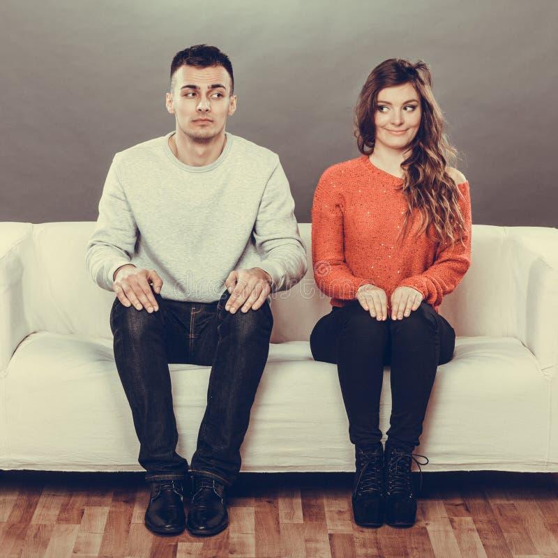 Donna timida ed uomo che si siedono sul sofà Prima data immagini stock libere da diritti