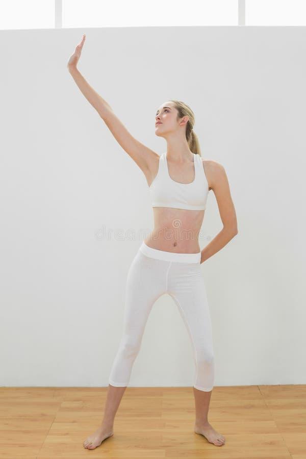 Donna tonificata adorabile che fa posa di yoga per l'allungamento del suo corpo fotografia stock libera da diritti