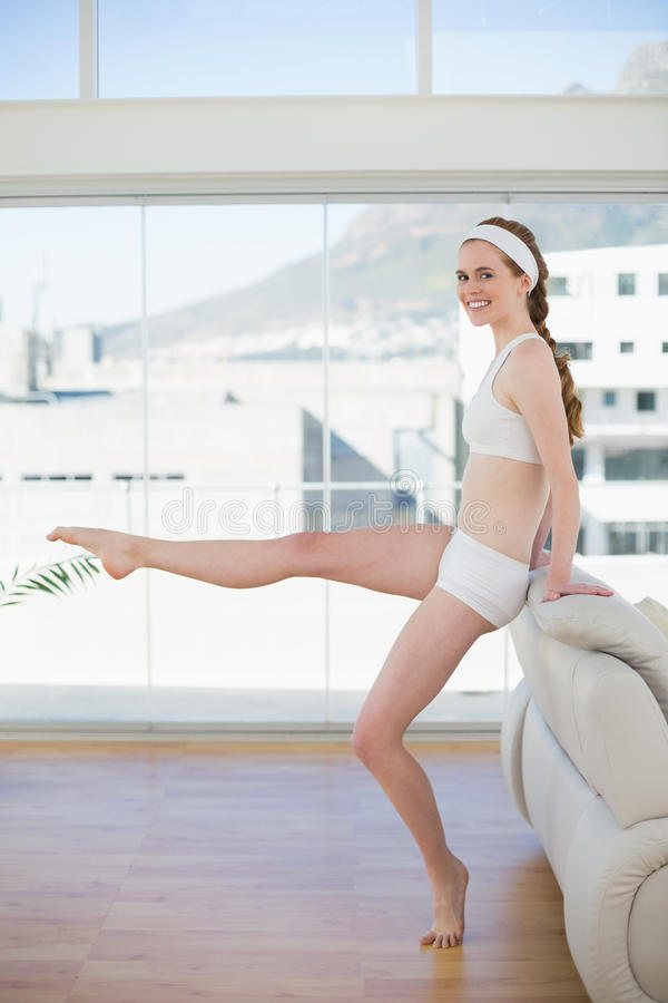 Donna tonificata che allunga gamba nel centro di forma fisica fotografia stock libera da diritti