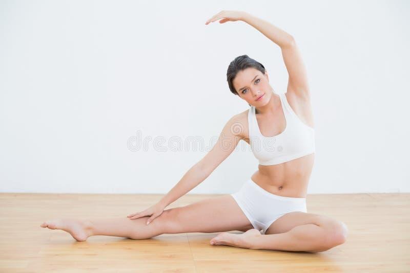 Donna tonificata che allunga mano e gamba nello studio di forma fisica fotografia stock