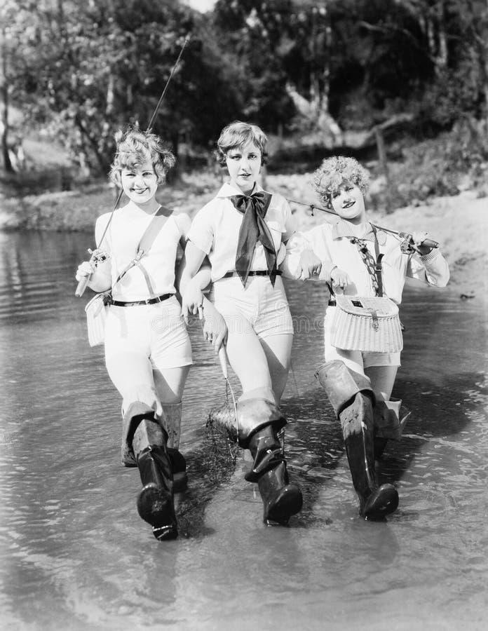 Donna tre che cammina con le canne da pesca attraverso una corrente (tutte le persone rappresentate non sono vivente più lungo e  fotografia stock libera da diritti