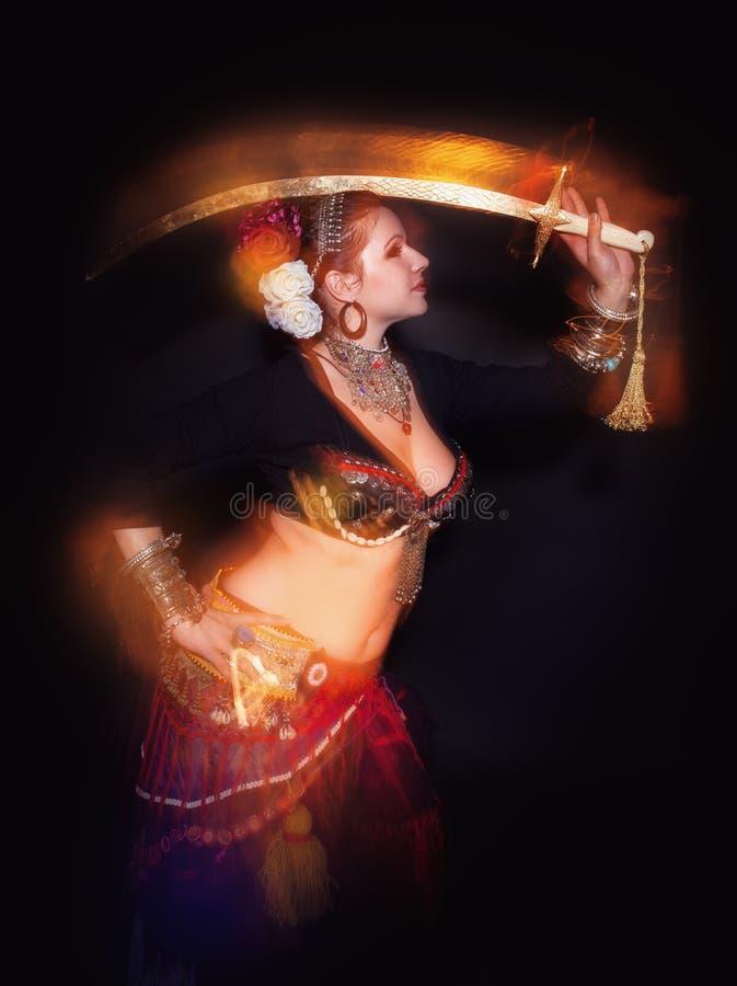 Donna tribale del ballerino della bella pancia esotica con la spada fotografie stock libere da diritti