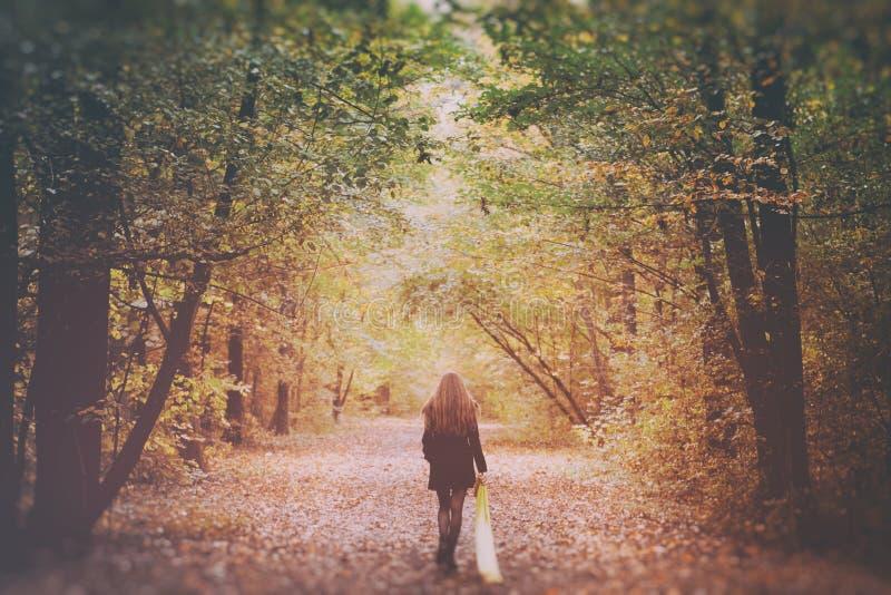 Donna triste che cammina da solo nel legno immagine stock libera da diritti