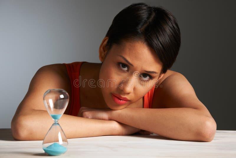 Donna triste che esamina clessidra fotografia stock libera da diritti