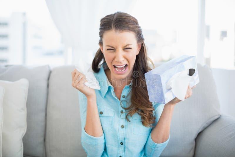 Donna triste che grida seduta sul sofà immagine stock libera da diritti